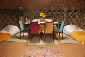 Bold colours and fresh flowers are a must for glamping in our handmade yurts.